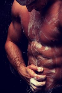 Handsome muscular man at the shower.